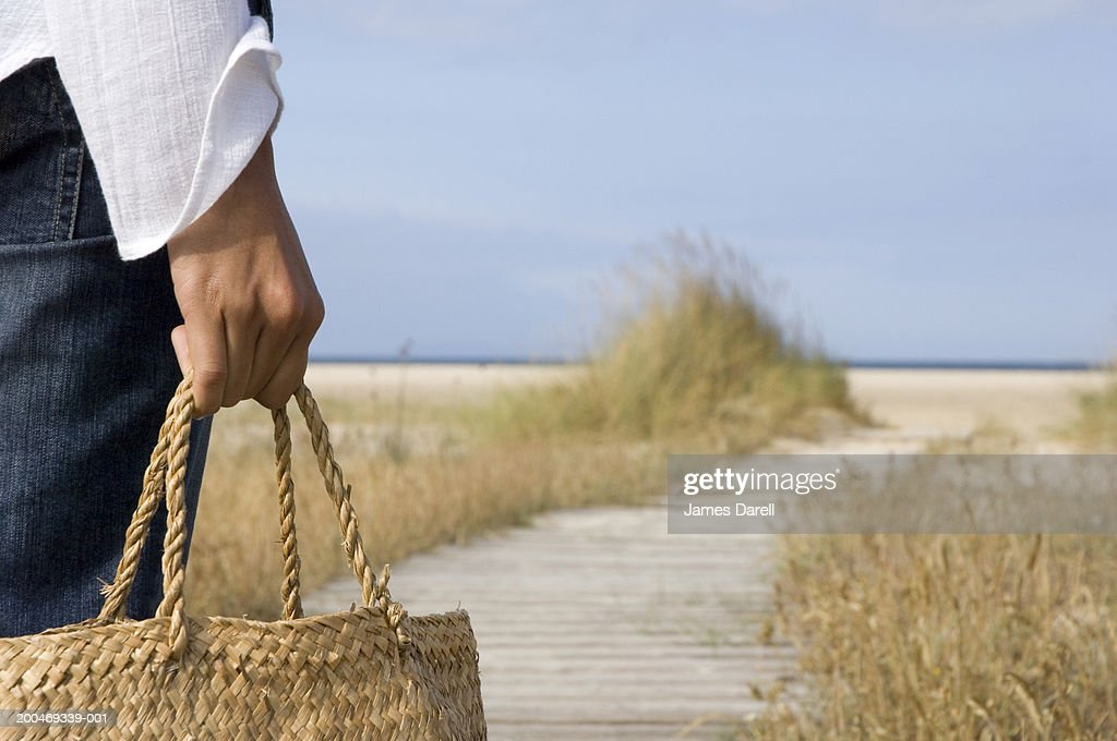 Woman on walkway leading to beach, mid section, rear view, close-up : Stock Photo