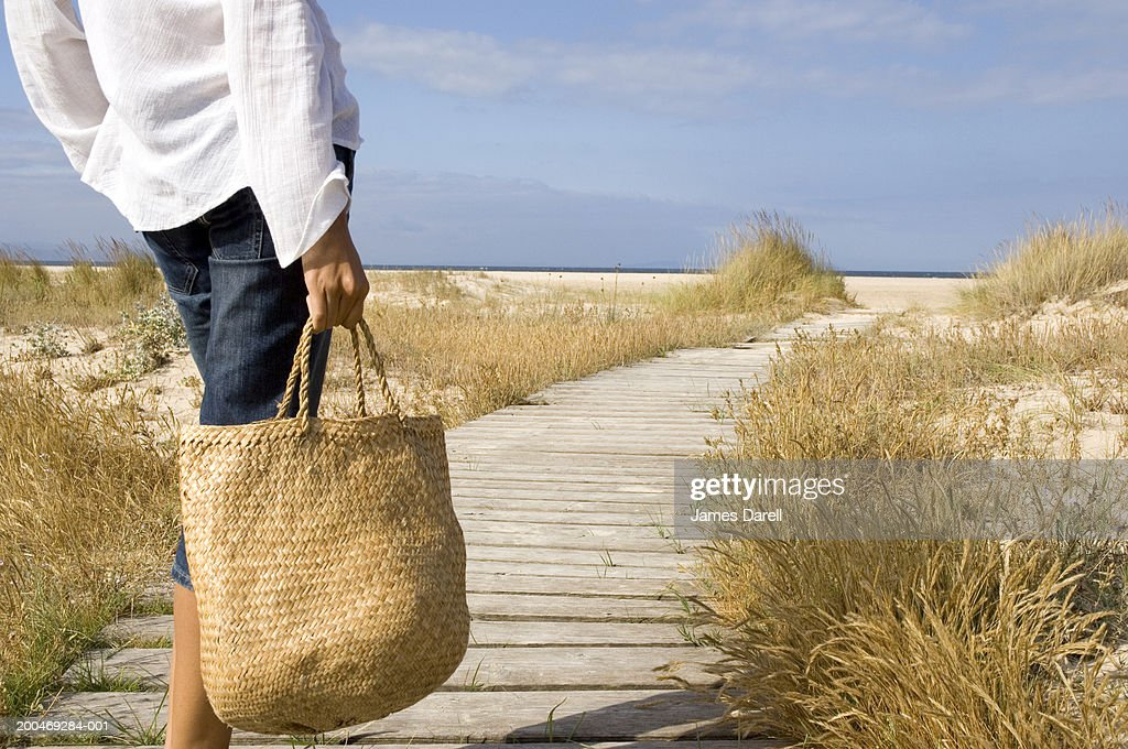 Woman on walkway leading to beach, mid section, rear view : Stock Photo