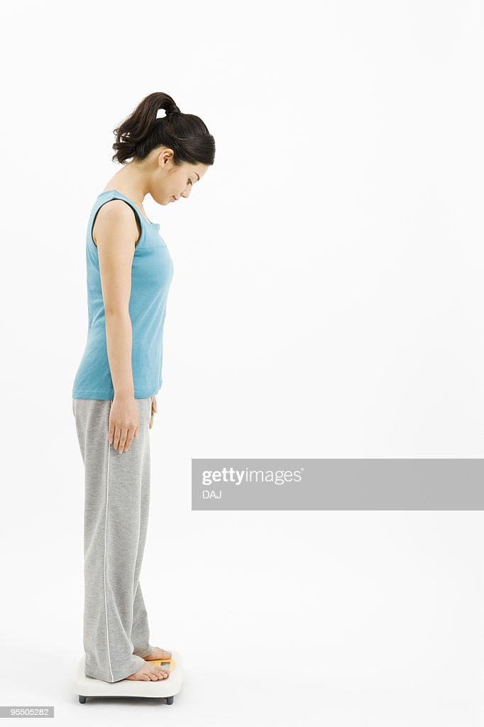 Woman on weight scale : Stock Photo