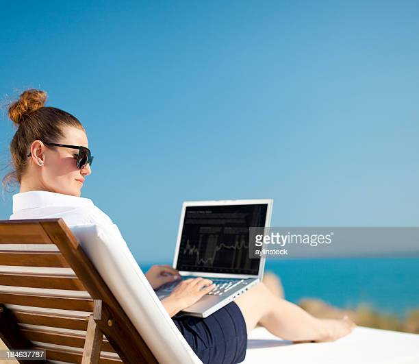 Woman on wooden lounge chair working on laptop at the beach