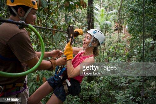 Woman on zip-line through rainforest canopy.