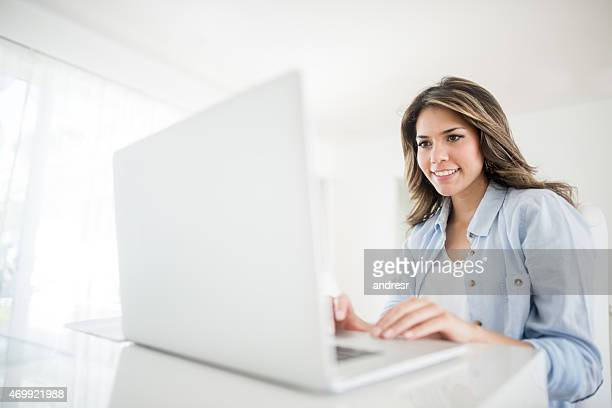 Woman online using a laptop at home