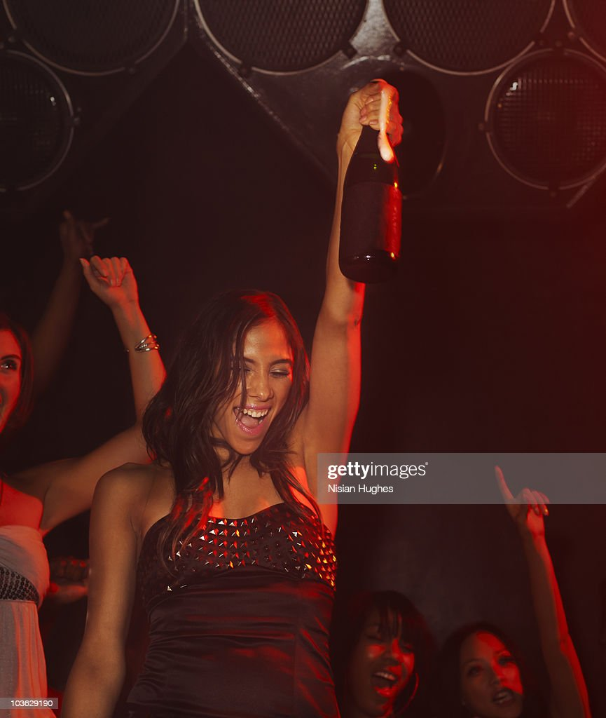 Woman opening a bottle of champagne at a nightclub : Stock Photo