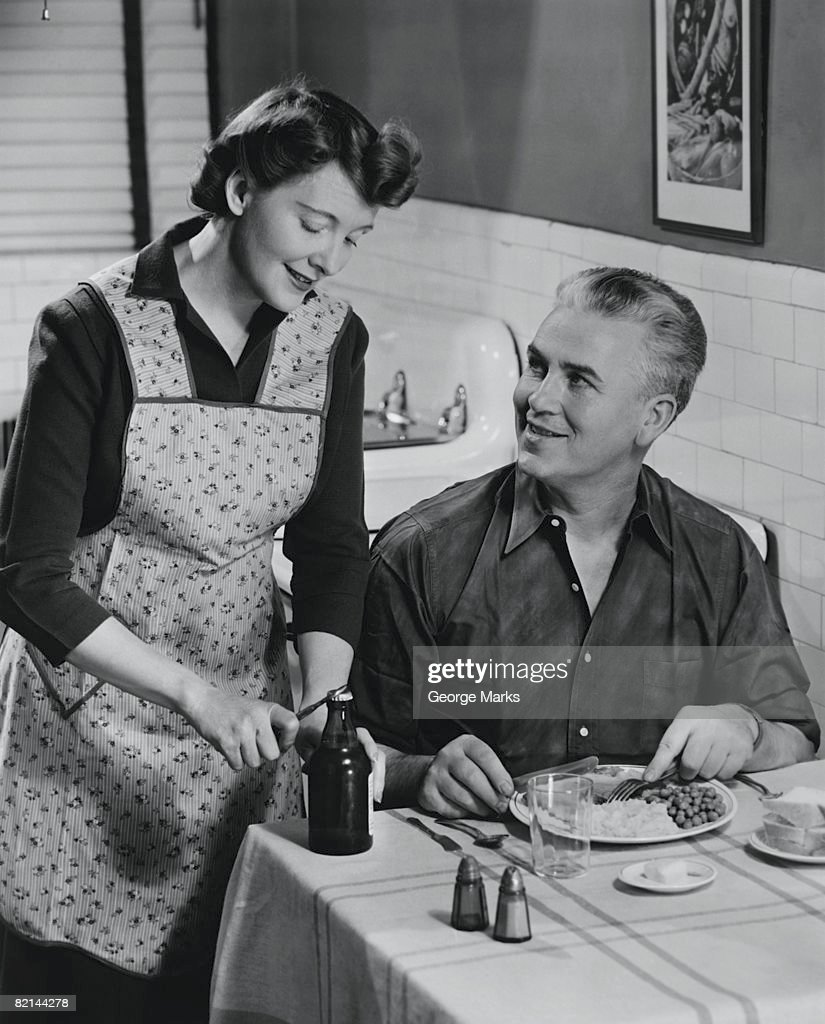 Woman opening beer bottle for man eating dinner, (B&W) : Stock Photo