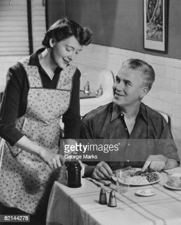 Woman opening beer bottle for man eating dinner, (B&W) : Stock Photo