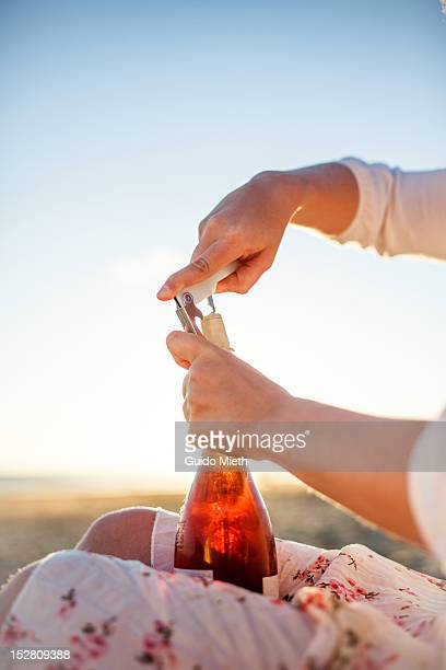 Woman opening bottle of wine at beach