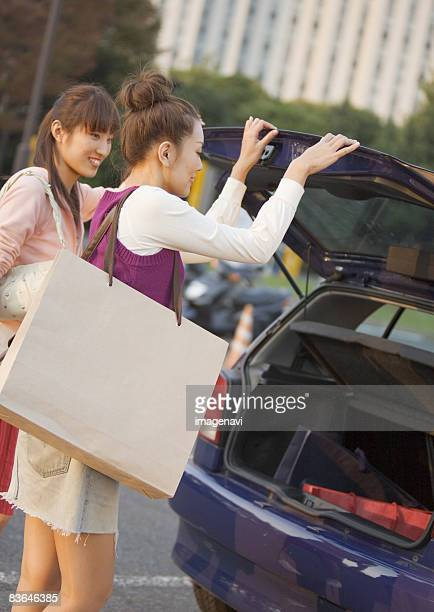 A woman opening car trunk