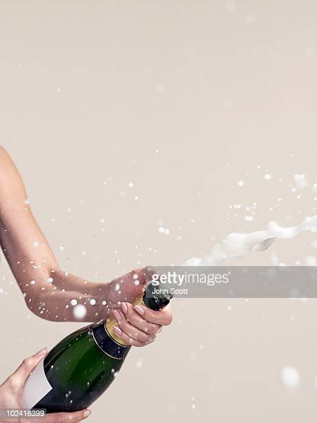 Woman opening champagne bottle