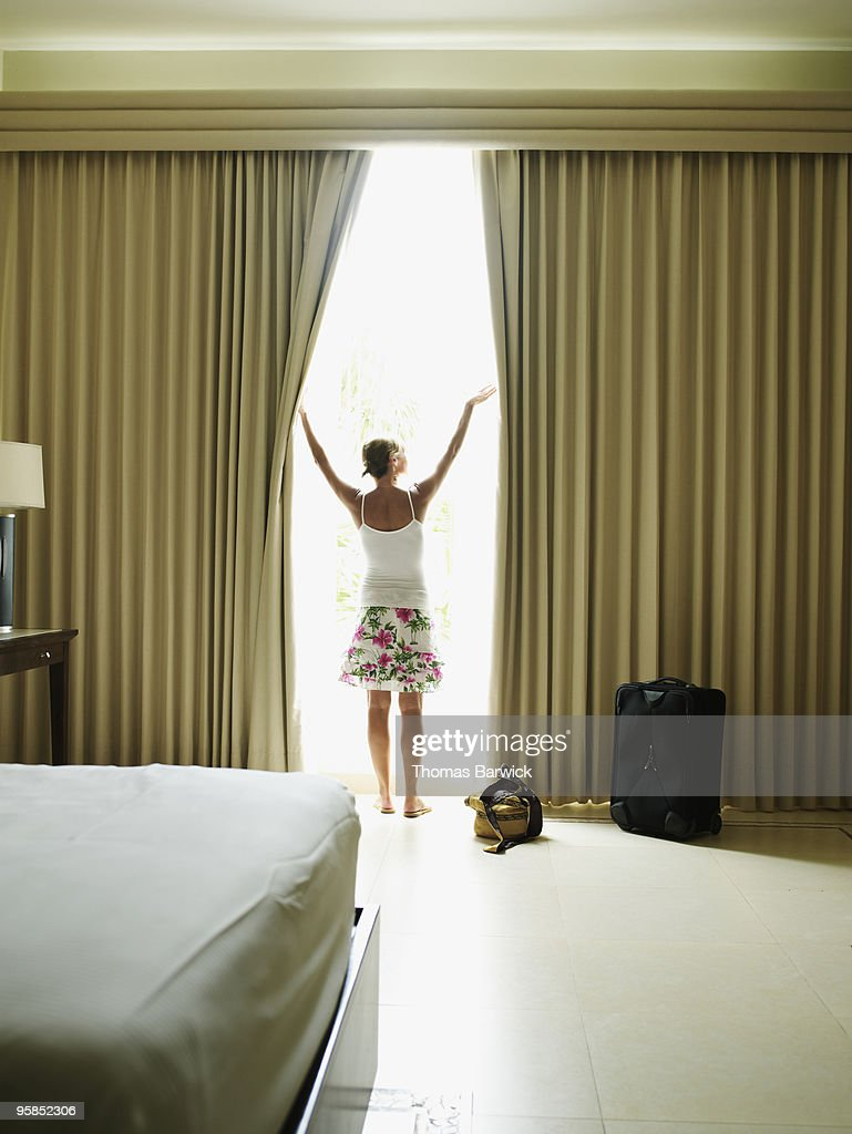 Hotel Room Photography: Woman Opening Curtains In Hotel Room Stock Photo