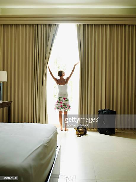 Woman opening curtains in hotel room