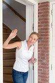 Woman opening door and waving, Goirle, Brabant, Netherlands