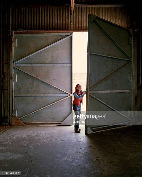 Woman opening door of warehouse
