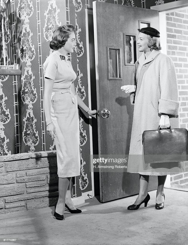Woman opening door to saleswoman. (Photo by H. Armstrong Roberts/Retrofile/Getty Images) : Stock Photo