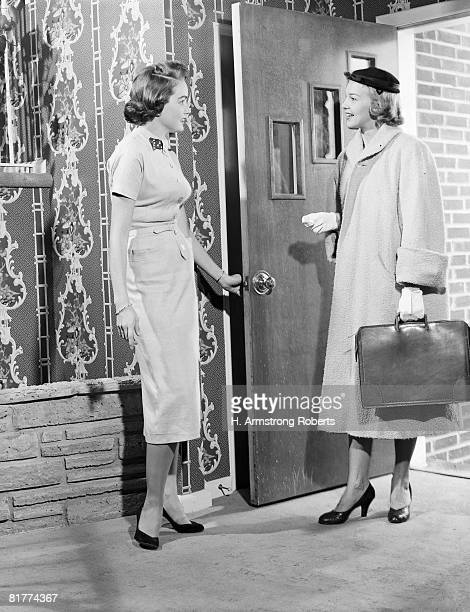Woman opening door to saleswoman. (Photo by H. Armstrong Roberts/Retrofile/Getty Images)