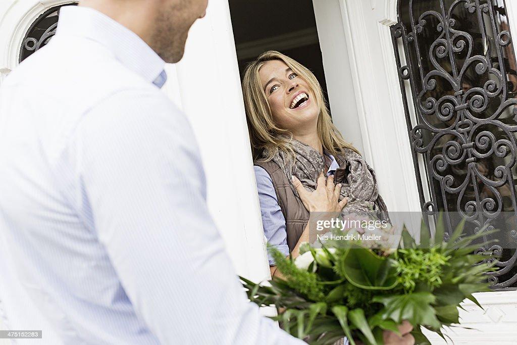 Woman opening front door, man with bouquet