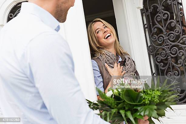 Woman opening front door, man with bouquet