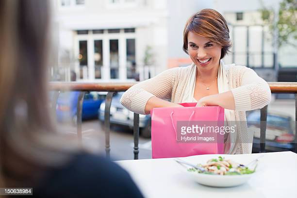 Woman opening gift at sidewalk cafe
