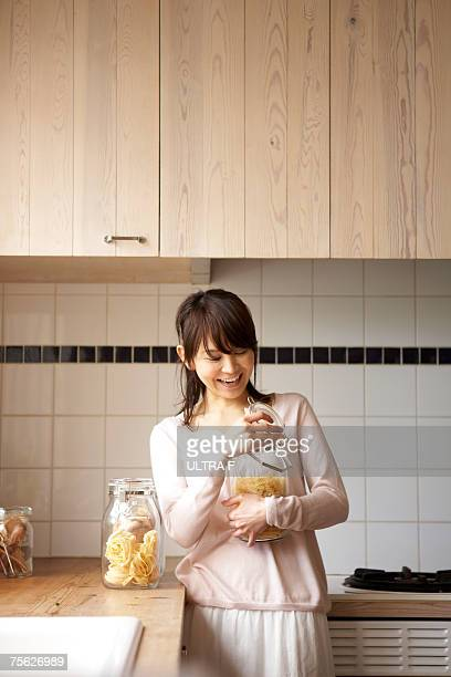 Woman opening glass jar of pasta in kitchen, smiling