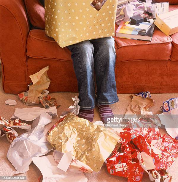 Woman opening presents, wrapping paper on floor, low section