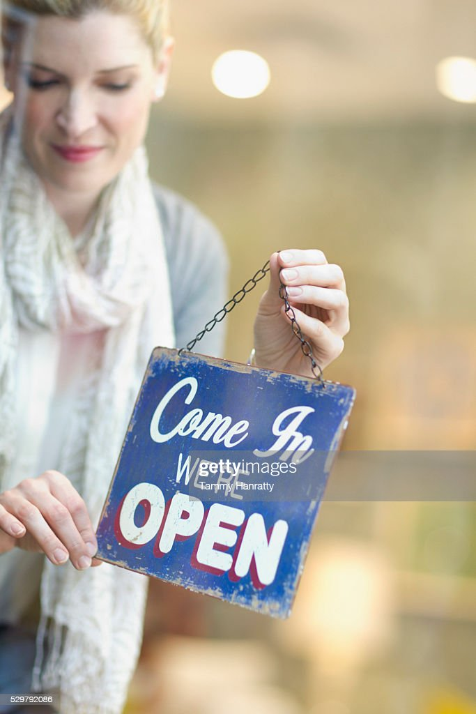Woman opening shop : Stockfoto