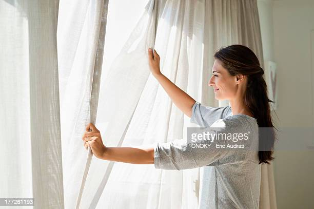 Woman opening the curtain of a window
