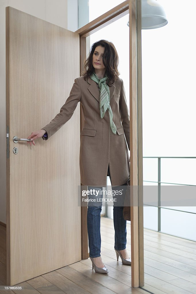 Woman opening the door of a house