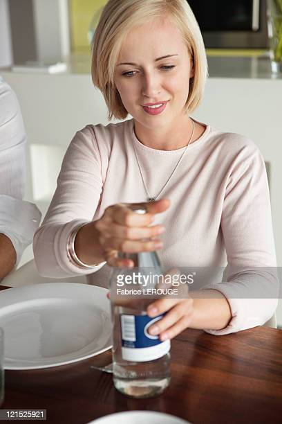 Woman opening water bottle at dining table