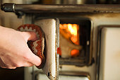 'Woman opening wood stove, close-up'