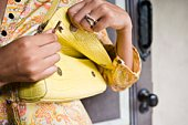 Woman opening yellow purse