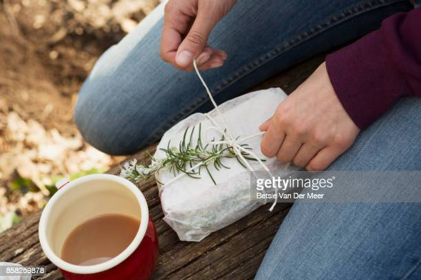 Woman opens packed lunch, sitting on tree trunk in forest.
