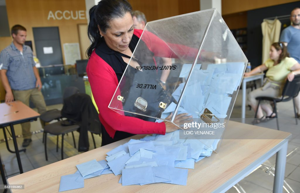 A woman opens the ballot box on June 26, 2016 in Saint-Herblain, outside Nantes, after a local referendum organised in Loire Atlantique regarding the transfer of the Nantes Atlantique airport to Notre-Dame-des-Landes. Nearly one million people living in France's Loire-Atlantique department voted in a referendum which poses the question 'Are you in favour of the project to transfer the Nantes-Atlantique airport to the municipality of Notre-Dame-des-Landes?' to voters. The referendum was organised by the French executive power hoping to find a solution to the issue which has dragged on for 50 years. / AFP / LOIC