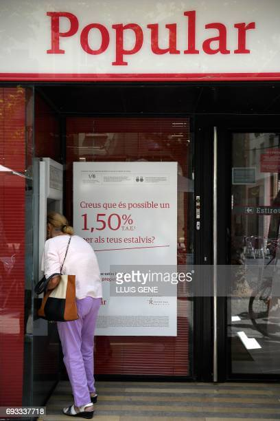 A woman operates at the ATM at a Banco Popular branch on June 7 2017 in Vilanova i la Geltru near Barcelona after European authorities announced the...