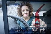 Woman operates car satellite navigation as seen through screen