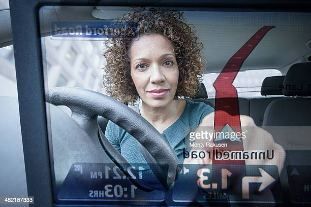 Woman operates car satellite navigation as seen through screen