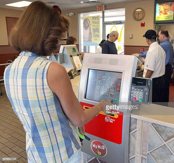 A woman orders a meal from a computerized kiosk as other patrons wait in line to place their order at the counter inside a McDonald's restaurant June...