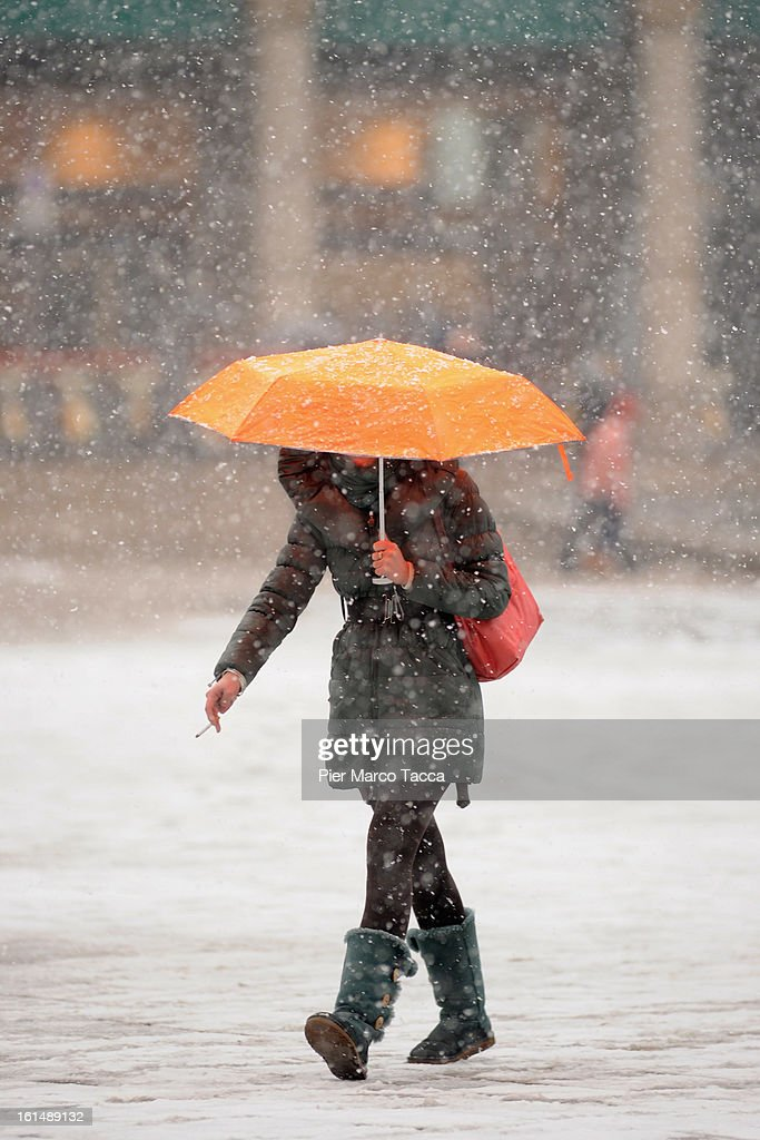 A woman out in the snow in Duomo square on February 11, 2013 in Milan, Italy.Wind, snow and tempetarture under zero over the country has affected regions from North Italy to South Italy, transports has been affected with train cancellations and road closures.