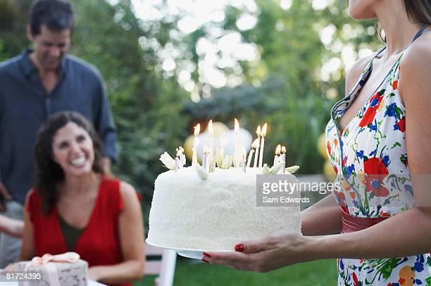 Frau im Freien tragen einen Geburtstagskuchen auf einem Lächeln Paar