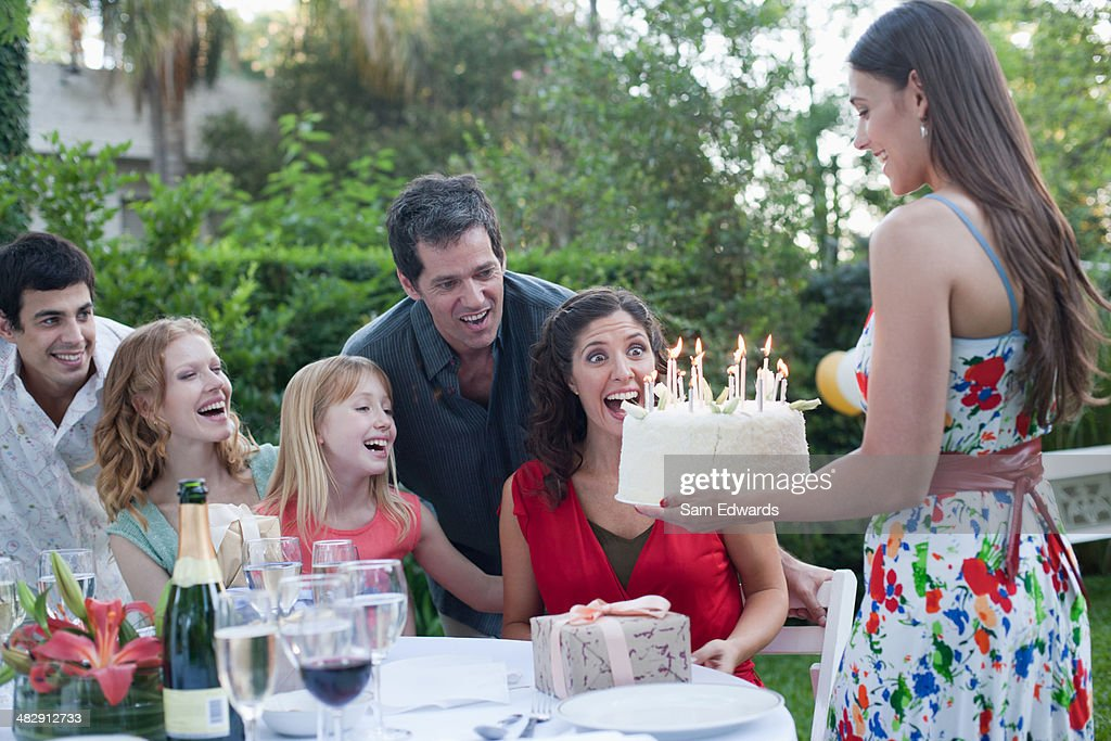 Woman outdoors carrying a birthday cake to a smiling people : Stock Photo
