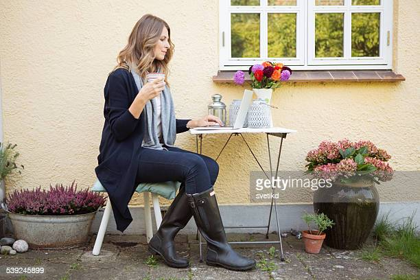 Woman outdoors in front of her house.