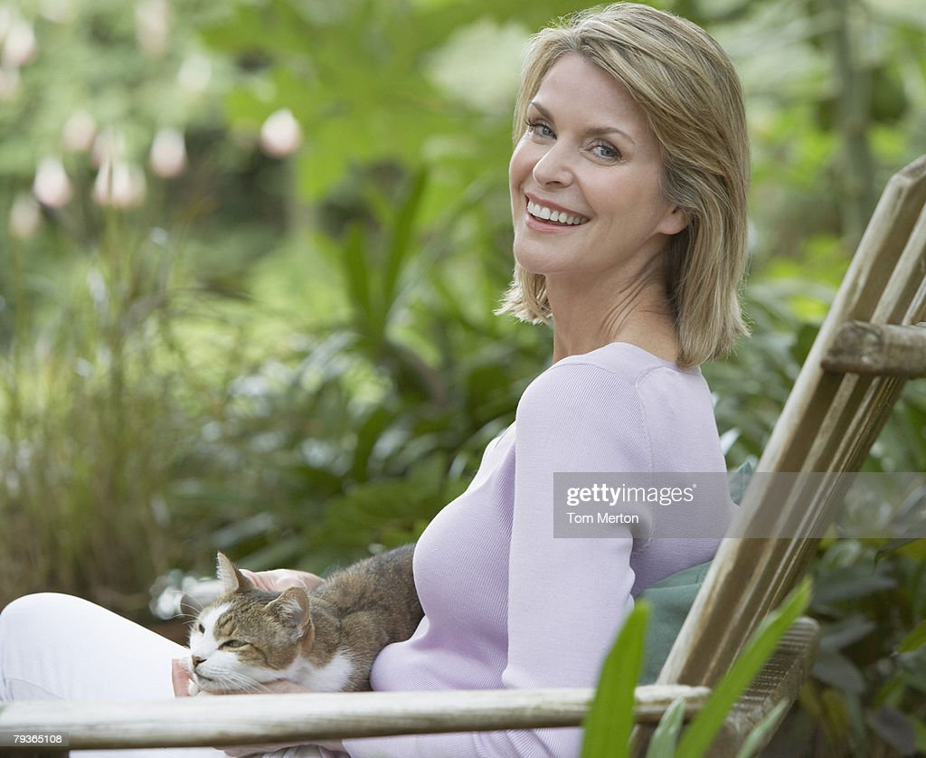 Woman outdoors in yard with cat on her lap : Stock Photo