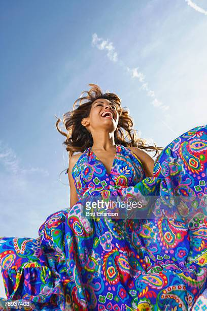 Woman outdoors laughing in a colorful dress.