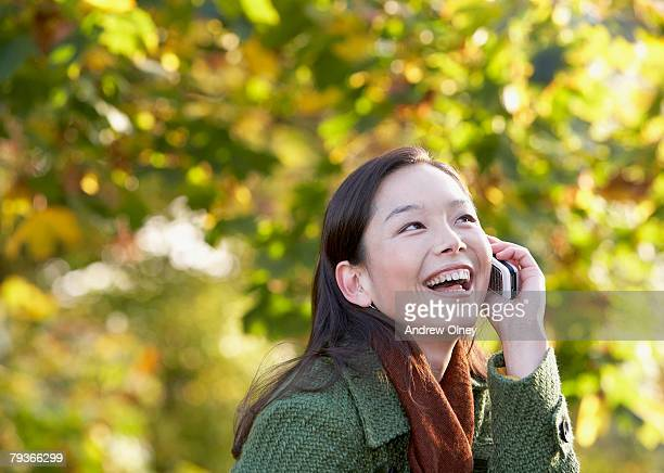 Woman outdoors on cellular phone laughing