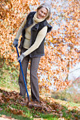 Woman outdoors raking leaves and smiling (selective focus)