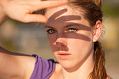 Woman outdoors shielding eyes