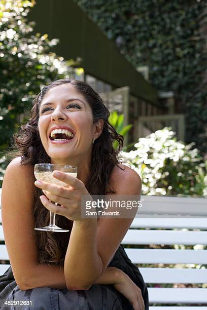 Woman outdoors sitting on bench with white wine laughing