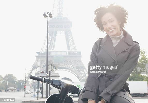 Woman outdoors sitting on scooter by the Eiffel Tower