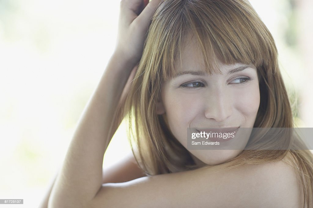 Woman outdoors smiling with hand in hair : Stock Photo