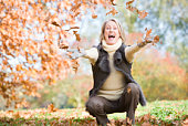 Woman outdoors throwing leaves up and smiling (selective focus)