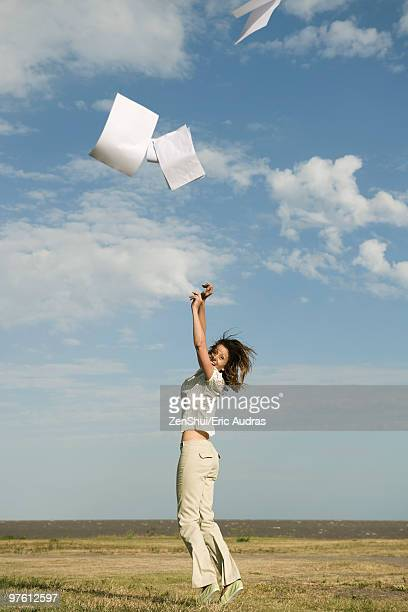 Woman outdoors tossing document into air
