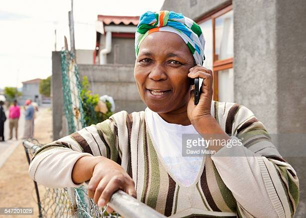 Woman outside her home talking on her mobile phone. Cape Town, South Africa